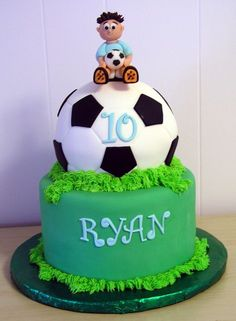 Personalized Soccer Cake featuring a pitch as the base with the name and a large round soccer ball on top featuring the age. A cute soccer player sits on top of the ball holding onto a smaller soccer ball - so cute!