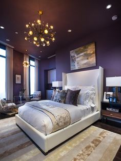A neutral area rug tones down the sultry plum found in the walls and ceiling and also provides a warm landing when getting out of bed in the morning.