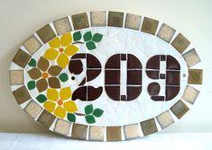 Numero residencial em mosaico, tamanho oval pequeno (30x20). Cliente pode escolher cor da borda e do número. O mosaico é realizado em cima de um piso de ceramica e deverá ser fixado na parede com argamassa. Ou poderá ser feito 2 furos para parafusar na parede, a pedido do cliente.