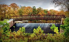 A steel pedestrian bridge across a water spillway at Lake Waterford Park in Pasadena, Maryland during Autumn. Subdued HDR toning, and other plugin effects were used to create a more pleasing ambience.
