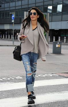 George Clooneys girlfriend Amal Alamuddin arrives at Heathrow Airport from Los Angeles.  Travel in comfort: Amal arrived at LAX in distressed boy jeans, a ribbed sweater, flats and some shades. Looks cool but comfy enough to relax while sipping gin 'n tonics and catching up on the latest SkyMall.