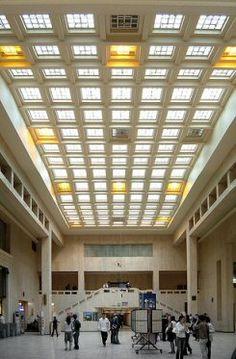 """De plan trapézoïdal, la """"Halte Centrale"""" occupe l'espace triangulaire formé par le Cantersteen, le boulevard de l'Impératrice et la Putterie. Si elle fut inaugurée en 1952, il faut savoir que le projet de construction remontait à 1910, quand on sollicita l'architecte Victor Horta pour concevoir cet accès aux voies ferroviaires. Les travaux, quant à eux, ne commencèrent qu'en 1937, après la réalisation de la jonction Nord-Midi. Maxime Brunfaut hérita du chantier à la mort de Horta, en 1947…"""