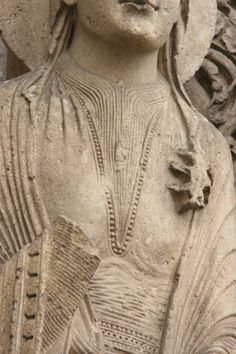 More pleating on neck of undergown and smock on the bliaut, Chartres east portal. One pinner opines: Stylized pleating and gathers - likely caused by lacing the bliaut.