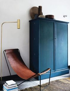 Modern Aesthetic. Simple blue armoir, leather sling chair. Books. Death by Elocution