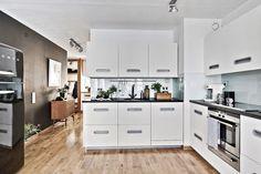Kök i vinkel med snygga vita spårfrästa köksluckor från Ballingslöv, bänkskiva i diamatborstad svart granit, kylskåp från SMEG. LUCKA: Zenus vit från serien Studio Ballingslöv