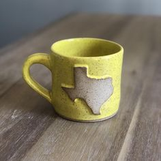 Handmade yellow Texas mug on speckled clay. Thrown on the pottery wheel. Made in Texas.