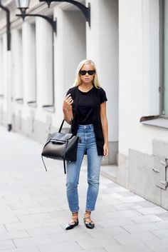 Black vest with high waist jeans, lace-up flats, and a Celine bag.