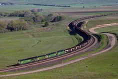 https://flic.kr/p/AWV5ST | Green Goodness | In May 1995, a Burlington Northern loaded coal train grinds through the lower horseshoe curve on Crawford Hill in Nebraska. Two BN C30-7s, and two BN SD40-2s lead the matching train through the temporarily lush landscape.