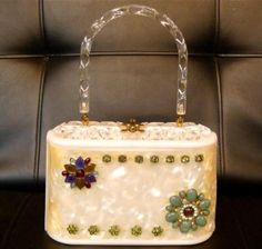 Whimsical Lucite Tote  Made of white marbleized acrylic, this box style handbag from the 1960s has been decorated by the current owner with vintage-era green agate clusters, sparkly rhinestones and colorful plastic jewels.  We think it's a great way to breathe new life into a retro accessory like this Lucite purse.