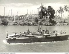 SEK ISLAND, NEW GUINEA. 1944-04-27. THE VIEW FROM THE CORVETTE HMAS BUNDABERG TOWARDS ALEXISHAFEN, SHOWING WRECKED BUILDINGS AT THE BACKGROUND, AND A UNITED STATES NAVY MTB (MOTOR TORPEDO BOAT) IN ...