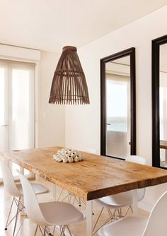 wood slab table in beachy white dining space by Tim Leveson