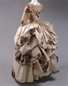 Rear view of Robe a la Polonaise, 1780, cream linen, gold embroidery, metal. (c) metropolitan museum of art: