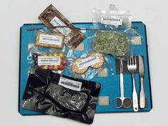 Bags of Space Station food and utensils on tray.