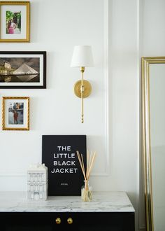 Traditional styling with a glam twist, featuring white walls, gold and black framed photos, marble countertops, gold wall sconces and black cabinets   hoo Interior Design & Styling