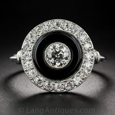 Platinum, Diamond and Onyx Art Deco Style Ring #10-1-7471 USD$3,450 A bright and shining European-cut diamond, weighing .37 carat, collet-set in platinum, centers a black onyx donut, surrounded in turn by a glittering diamond frame. A decorative openwork under gallery, a pair of diamonds on the shoulders and a striated ring shanks add the finishing flourishes to this strikingly stunning 'bulls-eye' sparkler, recently hand fabricated in platinum in faithful emulation of 1920s Jazz Age jewels.