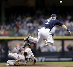 MILWAUKEE, WI - AUGUST 06: Scooter Gennett #2 of the Milwaukee Brewers cannot complete the double play to first base as Joe Panik #12 of the San Francisco Giants slides into second base at Miller Park on August 06, 2014 in Milwaukee, Wisconsin. (Photo by Mike McGinnis/Getty Images)