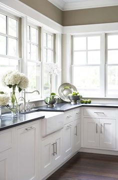 This kitchen by Linda McDougald Design sports 2 walls of windows, white cabinets and a dark countertop.