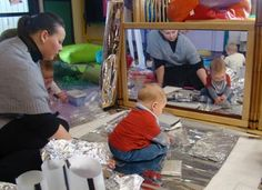 A Reggio Emilia infant classroom-- look at the exploration of materials! That baby is super engaged.
