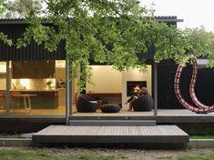 Terras met indirecte verlichting maken met loungekussens en centrale vuurschaal voor over vlek terras