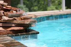 A small layered stone waterfall with water running down the unfinished edges of the red quartz.
