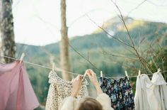 someone hanging up clothes, green, white, brown, blue, pink