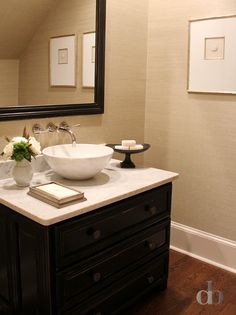 Tan and black powder rooms features walls clad in tan grasscloth lined with a distressed black dresser turned washstand topped with honed white marble topped with a white marble bowl sink under a wall-mount faucet under a black mirror.