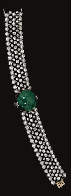 EMERALD AND DIAMOND BRACELET,  CIRCA 1915.  Centring on a circular cabochon emerald highlighted with circular- and single-cut diamond set motifs, to an articulated wide band designed as an open work mesh collet-set with circular-cut diamonds, within a millegrain-set scalloped border similarly set,  French assay marks.
