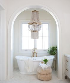 Arch over bathroom tub with chandelier.