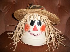 I love this little scarecrow head - and it's so easy!  Paint a large terra cotta pot with a cream-colored acrylic paint, add the face any way you want, and top with some straw hair and a straw hat.  So cute that I use this all fall.