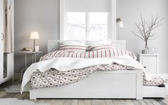 A white romantic bedroom with a white BRUSALI bed and bedside table, flowery PÄRLHYACINT quilt covers and LUDDE sheepskins.