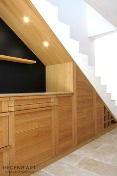Cuisine en bois massif, moderne aménagée sous un escalier avec avec niche éclairée et tableau ardoise. Rangements optimisés sous escalier by Hegenbart.fr