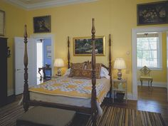 striped rug, geometric yellow and gray quilt, sunny yellow walls and a four poster with art over the doors in this Connecticut home ~ Bunny Williams design