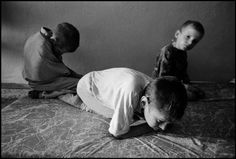 BELARUS. 1997. Novinki Asylum, Minsk. After breakfast these boys are placed on mats in a hall where they rock and huddle all day. Paul Fusco/Magnum Photos
