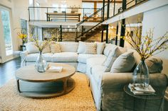 Neutral living spaces, like this one from Joanna Gaines on Fixer Upper, help your design stand the test of time. Add pops of colors with flowers and throw pillows. #fixerupper #magnoliafarms #joannagaines #magnoliahomes