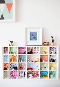 Adorable kid's bookshelf with different papers per shelf. (36 Brilliant Ways to Beautify Boring Bookshelves via Brit + Co.)