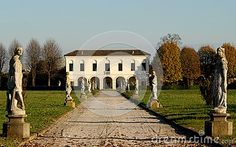 Photo made at a villa that was in Casalserugo a town in the province of Padua in Veneto (Italy). In the picture taken by the outer gate of the villa we see the wide central avenue, with light-colored gravel and statues on the sides, which leads between two large green lawns at the entrance to the porch of the house. Picture, overall, the white house framed by the trees, which are located on both sides, and the blue sky.
