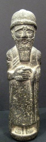 Assyrian Stone Sculpture of a Standing King -  Origin: Mesopotamia Circa: 900 BC to 600 BC Dimensions: 9.5 (24.1cm) high x 2.25 (5.7cm) wide Collection: Near Eastern Medium: Stone