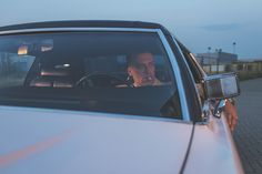 A man smoking a cigarette in a vintage car