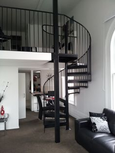 Elegant Black Corner Stairs with Open End Angled Treads and Standard Iron Balusters also Round Metal Handrail for Space Saver Spiral Staircase Design Ideas