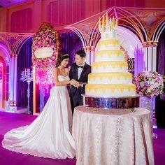 Sabia que é possível fazer seu casamento na Disney? Clique para ver os pacotes e valores! Na foto, bolo de casamento de vários andares com topo de bolo de castelo.