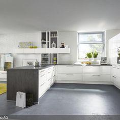 Diese offene Küche mit weißen Schränken wirkt einladend und strahlt eine angenehme Cleanness aus. Angrenzend befindet sich ein Wohnbereich mit gelbem Teppich.…