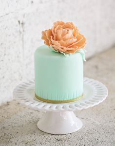These two colors collaborate beautifully with one another. I love the wrinkles at the bottom of the cake and how it adds definition. The gold ribbon and flower tops off the whole cake elegantly. @GraceJT29