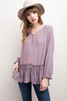 Long sleeve V-neckline button down with ruffled hem, bohemian inspired tunic top. Content + Care: 100% Rayon Hand Wash