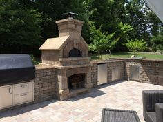Custom outdoor kitchen with pizza oven, firepit and patio.