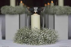 Wedding lantern with candle and a base wreath of gypsophila, by Exclusively Weddings. Photo by Martin bell