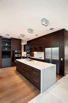 This kitchen has a mix of dark wood cabinets and light wood floors, with white countertops to tie it all together.