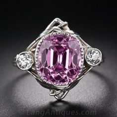 A ring from the Arts & Crafts design period - circa 1890-1914. This singular creation radiates with an entrancingly natural pink sapphire, weighing 7.40 carats, with a very subtle lavender overtone. The gemstone is set in a milgrained bezel and is accompanied on each side by a sparkling old mine-cut diamond. All three stones are entwined by a sinuous, leafy morning glory design artfully overlaid in platinum. A romantic treasure most likely of English origin. In a finger size 7 3/4.