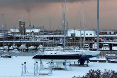 The Clock Tower and Granville Dock under Snow, Dover Marina, Kent, England, UK. Crosswall Quay runs across centre in front of which are yachts and boats in non-tidal Granville Dock; right-of-centre is Dover Lifeboat Station building. Between quay and Clocktower is the Tidal Harbour. Behind tower is smoke from the MS Spirit of Britain cross-English Channel ferry (P and O Ferries) en route to Calais, France. Winter 2013 (January). Travel and Tourism. See…