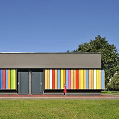 Slovenian studio Arhitektura Jure Kotnik have completed this colourful extension to a Kindergarten in Ljubljana. Called Kindergarten Kekec, the building has rotating vertical shutters over the glazed facade, painted in bright colours on one side and plain wood on the other.
