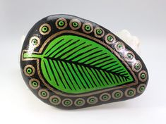 I am painting rocks as a healing art. This one-of-a-kind mandala inspired stone features a green leaf on black with bronze accents. It makes a unique gift for a coworker, friend or loved one. My hand painted stones are perfect paperweights, house warming gifts, coffee table decorations